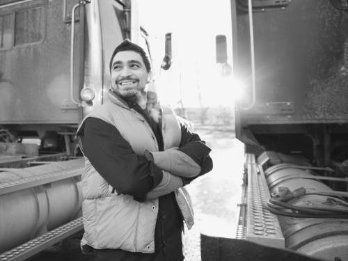 Happy truck driver standing next to cab