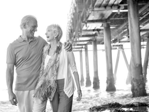 Retiree couple walks on beach under pier