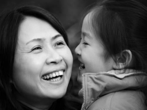Asian mother holding daughter