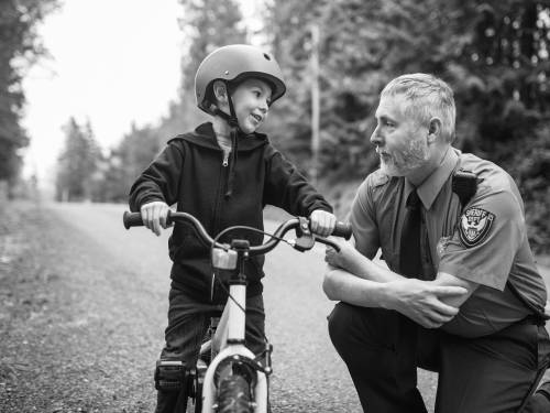 police office speaking with kid on bike